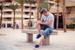 Mann mit Knieschmerzen sitzt auf einer Bank
