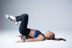 Frau liegt auf dem Rücken und macht physiotherapeutische Übung mit einer Fazienrolle